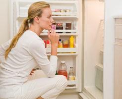 Woman looking inside refrigerator